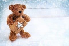 Poco oso de peluche con un regalo de la Navidad que se coloca en un azul blanco Imagen de archivo libre de regalías