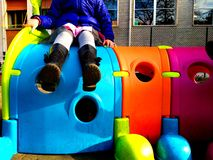 Poco otudoor el jugar de niño en un patio con un juguete, una diversión y un concepto coloridos del juego fotos de archivo