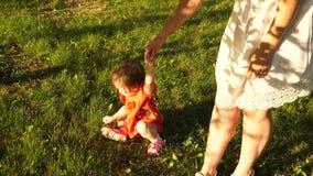 Poco paseo de la hija y de la madre en césped El bebé detiene a la mamá a mano y rasga apagado la hierba de verde el niño camina  almacen de metraje de vídeo