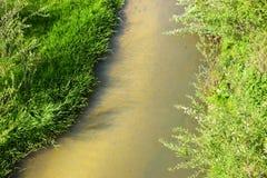 Poco pesca en el pequeño río en un día soleado de la primavera imagenes de archivo