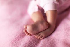 Poco piernas dulces del bebé en fondo rosado Concepto: niños, paternidad, familia, fiesta de bienvenida al bebé Copie el espacio  fotos de archivo libres de regalías