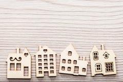 Poco pueblo de las figuras de madera de la casa en una superficie en madera Imagenes de archivo
