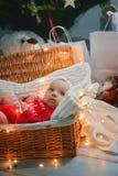 Poco que desliza al bebé con ropa de la Navidad en la decoración de la Navidad de la cesta y luces de destello alrededor de ella foto de archivo libre de regalías