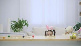 Poco que juega al niño con los oídos del conejito en su cabeza está ocultando debajo de la tabla de madera, llena de decoraciones