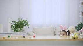 Poco que juega a la muchacha con los oídos del conejito en su cabeza está ocultando debajo de la tabla de madera, llena de decora