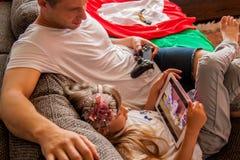 Poco que la muchacha linda est? utilizando la tableta, su padre est? jugando la consola fotos de archivo