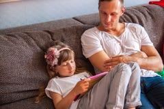 Poco que la muchacha linda est? utilizando la tableta, su padre est? jugando la consola fotografía de archivo