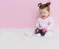 Poco que una niña pequeña se sienta y que juega con los zapatos del ` s de los niños Fotos de archivo libres de regalías