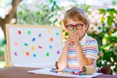 Poco ragazzo del bambino della scuola con i vetri che tengono i pastelli di cera Fotografie Stock Libere da Diritti