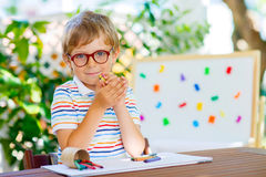 Poco ragazzo del bambino della scuola con i vetri che tengono i pastelli di cera Fotografie Stock