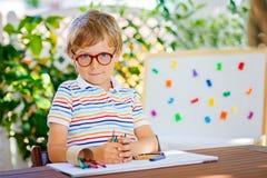 Poco ragazzo del bambino della scuola con i vetri che tengono i pastelli di cera Immagine Stock