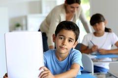 Poco ragazzo di scuola che mostra taccuino in bianco Fotografia Stock Libera da Diritti