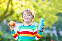 Poco ragazzo di scuola con la bottiglia dei libri, della mela e della bevanda Immagine Stock