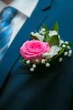 Poco ramo de flores rojas y blancas en el bolsillo del gro Fotos de archivo