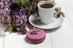 Poco ramo elegante delicado de flores de la primavera y una taza de t? en la tabla de madera blanca, desayuno de la ma?ana foto de archivo