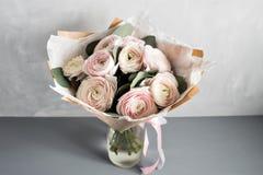 Poco ramo elegante delicado de flores, de ranúnculos y de eucalipto en lata y de una taza de té en la tabla gris blanca fotografía de archivo libre de regalías