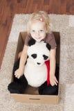 Poco sonríe muchacha en un cardbox con su oso de peluche Fotografía de archivo libre de regalías