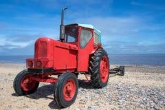 Poco tractor diesel rojo viejo en la playa imágenes de archivo libres de regalías
