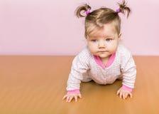 Poco una niña pequeña con las colas de caballo en la cabeza que se arrastra en el piso Foto de archivo