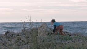 Poco vagabundo contra el fondo del mar piedras que lanzan del pequeño huérfano del muchacho en la orilla en tiempo ventoso homele almacen de video