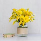 Poco vecchio libro, un mazzo dei crisantemi dei fiori, verga aurea e margherite in un vaso di vetro casalingo Fotografia Stock Libera da Diritti