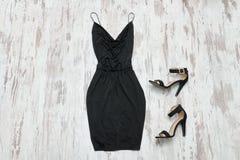 Poco vestido y zapatos negros Fondo de madera, estafa de moda Imagen de archivo libre de regalías