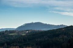 Poco villaggio, campi e foreste e una chiesa sulla collina Immagini Stock