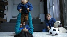 Poco vuelo del bebé con la ayuda de las manos de la mamá metrajes