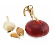 Pocos clavos del ajo y de la cebolla roja Fotografía de archivo