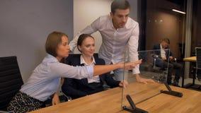 Pocos empresarios trabajan con la exhibición de cristal transparente futura moderna del interfaz almacen de video