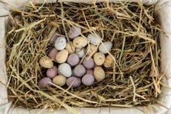 Pocos huevos de Pascua del caramelo en una cesta Fotos de archivo libres de regalías