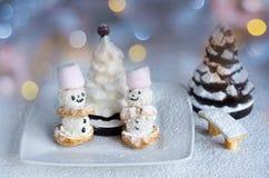 Pocos muñecos de nieve de las tortas y árboles de chocolate en azúcar en polvo En el fondo del bokeh colorido Fotos de archivo libres de regalías