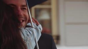 Pocos tiros de los pares adorables que giran, risa, abrazando en la ciudad debajo del paraguas Mujer bastante joven en un casual almacen de video