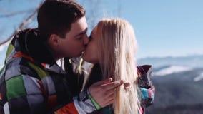 Pocos tiros de pares jovenes hermosos encima de la montaña nevosa, él toca su pelo rubio, ellos se está besando blando almacen de metraje de vídeo