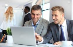 Początkowa biznes drużyna na spotkaniu w nowożytnym jaskrawym biurowym wnętrzu i działanie na laptopie obraz stock