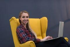 Początkowy biznes, kobieta pracuje na laptopie na kolorze żółtym i obsiadanie, Zdjęcie Stock