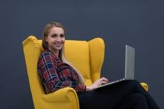 Początkowy biznes, kobieta pracuje na laptopie na kolorze żółtym i obsiadanie, Obraz Stock