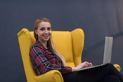 Początkowy biznes, kobieta pracuje na laptopie na kolorze żółtym i obsiadanie, Obrazy Royalty Free