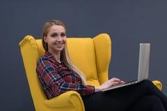 Początkowy biznes, kobieta pracuje na laptopie na kolorze żółtym i obsiadanie, Obraz Royalty Free