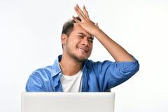 Początkowy biznesowy mężczyzna chlasta jego głowę w stresie podczas gdy pracujący na laptopie Obraz Royalty Free
