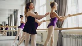Początkujący baletniczy tancerze lerning podnosić nogi zacofanego mienia baletniczego barre podczas gdy poważny nauczyciel daje zbiory wideo