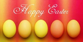 Pocztówka z pięć biologicznymi organicznie czerwonymi pomarańczowego koloru żółtego Easter jajkami na tęczy tle zdjęcie stock