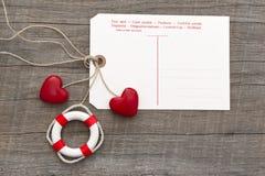 Pocztówka dla wiadomości z dwa czerwonymi sercami i lifebuoy na popielatym w Obraz Royalty Free