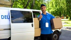 Pocztowy urzędnik bierze pakuneczka pudełko od doręczeniowego samochodu dostawczego i pokazuje aprobaty zdjęcie stock