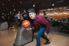 Poczynać młodego człowieka iść rzucać piłkę dla rzucać kulą Studenccy bawić się kręgle Spojrzenie przy kamerą Zdjęcia Stock