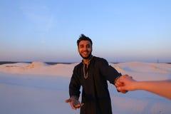 Podąża ja Arabski facet i europejczyk kobieta która chodzi ręką w deserze Fotografia Stock