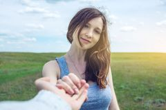 Podąża ja, Atrakcyjna brunetki dziewczyna trzyma rękę prowadzenia w czystym zieleni polu, step z chmurami fotografia stock