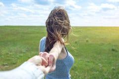 Podąża ja, Atrakcyjna brunetki dziewczyna trzyma rękę prowadzenia w czystym zieleni polu, step z chmurami fotografia royalty free