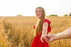 Podąża ja, Piękni seksowni młoda kobieta chwyty ręka mężczyzna w pszenicznym polu Fotografia Royalty Free