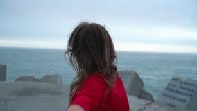 Podąża ja ręka w rękę chodzący latarnia morska na plaży przy - szczęśliwa młoda kobieta w czerwieni sukni ciągnięcia faceta ` s r zdjęcie wideo